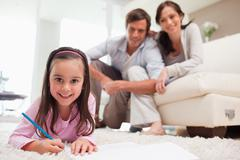 Cute girl drawing with her parents in the background - stock photo