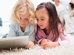 Children using a tablet computer while their parents are in the background - stock photo