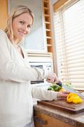 Smiling woman slicing pepper bell - stock photo