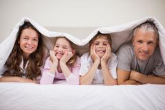 Playful family lying under a duvet - stock photo