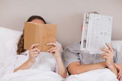 Woman reading a book while her companion is reading a newspaper Stock Photos