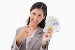 Stock Photo of Smiling businesswoman pointing at her money
