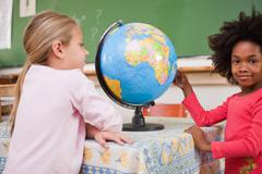Stock Photo of Cute schoolgirls looking at a globe