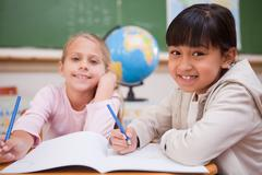 Smiling schoolgirls doing classwork Stock Photos