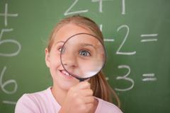 Stock Photo of Playful schoolgirl looking through a magnifying glass