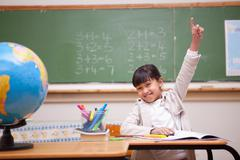 Schoolgirl raising her hand to answer a question - stock photo