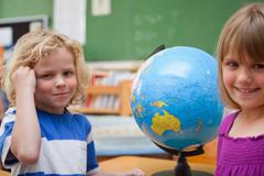 Stock Photo of Pupils posing in front of a globe