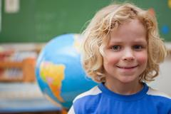 Stock Photo of Schoolboy posing in front of a globe