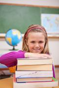 Portrait of schoolgirl posing with books - stock photo