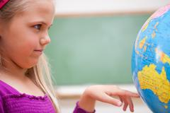 Close up of a schoolgirl looking at a globe - stock photo