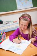 Stock Photo of Portrait of a cute schoolgirl drawing