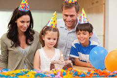 Girl about to blow out the candles on her birthday cake Stock Photos