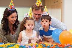Boy helping his little sister to blow out the candles on her birthday cake Stock Photos
