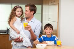 Stock Photo of Father having breakfast with his kids