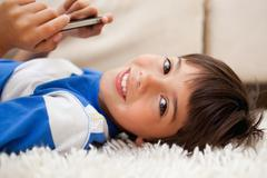 Boy lying on the carpet with cellphone - stock photo