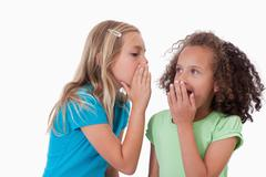 Cute girl whispering a secret to her friend - stock photo