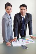 Portrait of smiling sales persons studying their results - stock photo