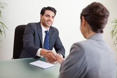 Smiling manager interviewing a female applicant - stock photo