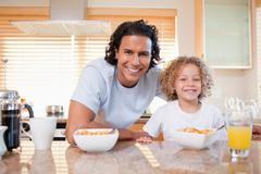 Stock Photo of Father and daughter having cereals in the kitchen together