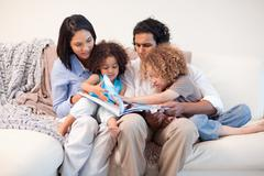 Stock Photo of Family on the sofa looking at photo album together