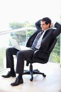 Portrait of a relaxed businessman sitting on an armchair working with a laptop - stock photo