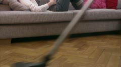 A pregnant woman lying on a couch and a man vacuuming Stock Footage