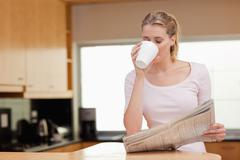 Stock Photo of Woman reading the news while having coffee