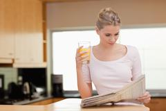 Stock Photo of Woman reading the news while drinking orange juice
