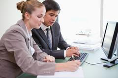 Stock Photo of Young business people working with a computer