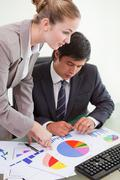 Portrait of a serious business team studying statistics with a computer - stock photo