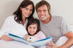 Smiling parents reading a story to their daughter Stock Photos