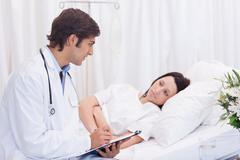 Doctor talking to his patient that just woke up - stock photo
