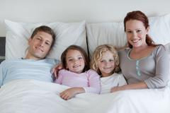 Family sharing the bed - stock photo