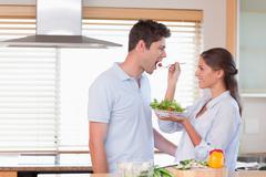 Happy couple tasting a salad - stock photo