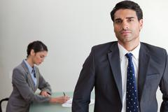 Handsome businessman posing while his colleague is working Stock Photos