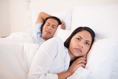 Woman lying awake next to her sleeping boyfriend Stock Photos