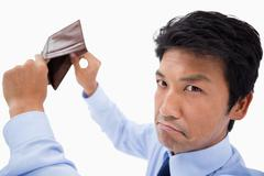 Broke businessman showing his empty wallet - stock photo