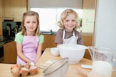 Stock Photo of Smiling siblings preparing dough