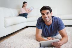 Mies käyttää tablet tietokonetta, kun hänen sulhasensa lukee kirjaa Kuvituskuvat