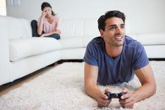 Stock Photo of Man playing video games while his girlfriend is getting mad at him