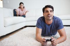 Man playing video games while his fiance is getting mad at him - stock photo