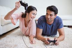 Stock Photo of Woman beating her fiance while playing video games