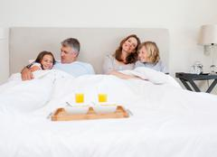 Family about to have breakfast in bed - stock photo