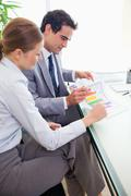 Side view of colleagues analyzing statistics together - stock photo