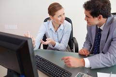 Trading partner sitting behind a desk while talking - stock photo