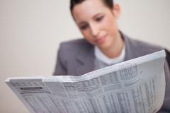 Newspaper being read by businesswoman - stock photo