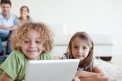 Smiling children using a tablet computer while their happy parents are watching - stock photo