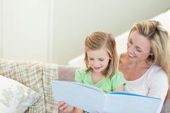 Mother and daughter reading a magazine Stock Photos