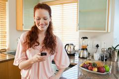 Woman in the kitchen writing text message Stock Photos