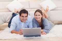 Stock Photo of Cute couple posing with a laptop